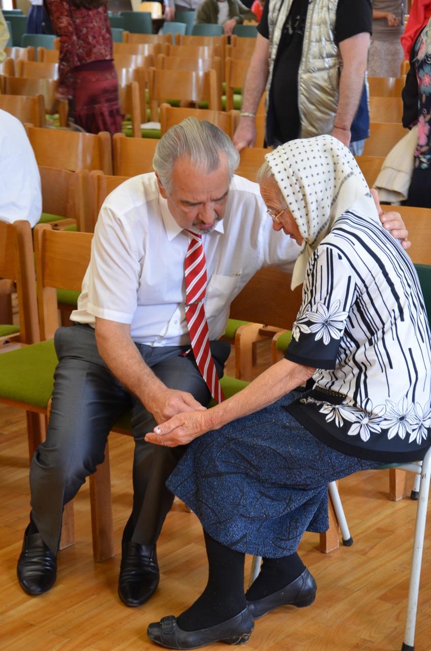 Alexander K. betet mit einer älteren Frau.